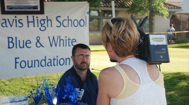 """Will Arnold being interviewed by a person holding a camera. The sign behind him reads """"Davis High School Blue & White Foundation"""""""