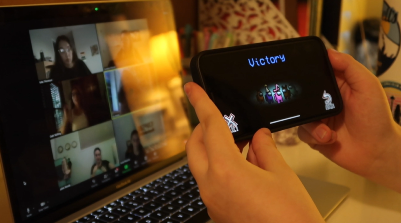 A student holding up a phone with the victory screen from the game Among Us in front of a Zoom meeting on a laptop