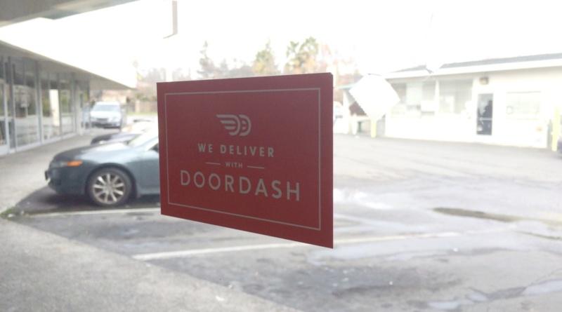 Doordash sign on a window facing a parking lot