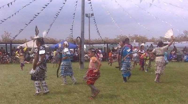 A Native American tribe celebrating indigenous cultures by dancing