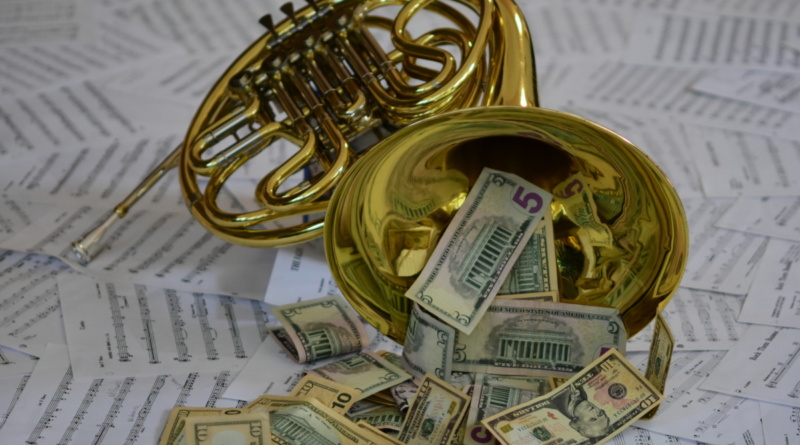 Money spilling out of a French horn on top of scattered music sheets