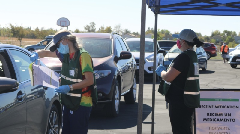 A volunteer dispenser checking a patient's paperwork in front of a line of cars