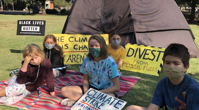 "Five kids wearing face masks sit in the grass on a blanket. They are in front of a tent which insinuates that they are camping out and they are holding climate activism signs that say things like ""divest from fossil fules"" and ""climate strike, Fridays 12-1 central park"""
