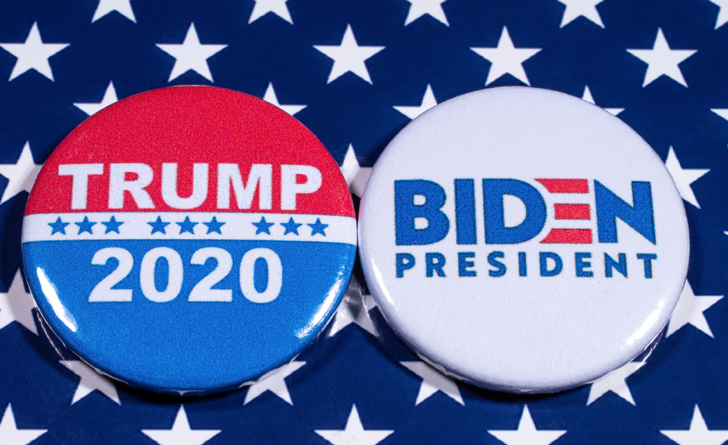 "Two buttons reading ""Trump 2020"" and ""Biden president"" displayed on top a blue tablecloth with white stars"