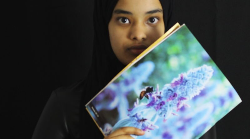 Senior Omnia Ali holding up her previous photography Spoke submissions