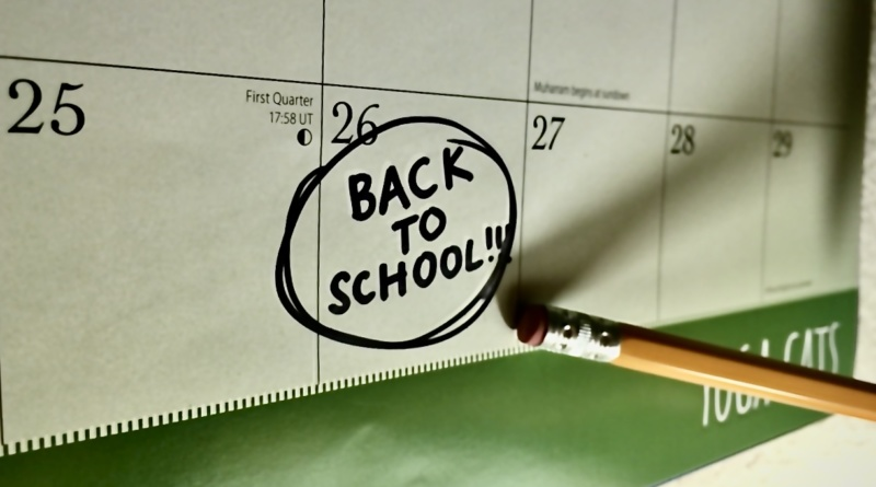"""The back of a pencil points to the date Aug. 26 marked with a circled """"back to school"""" in black ink"""