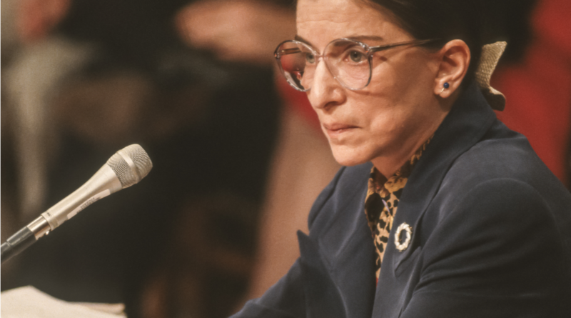 Justice Ruth Bader Ginsburg sitting with arms crossed in front of a microphone