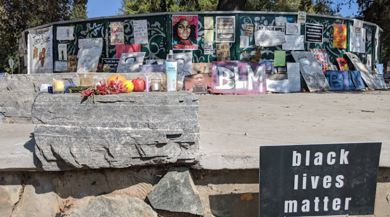 """Community artwork covering a gate in Central Park with a """"black lives matter"""" sign in the bottom right corner"""