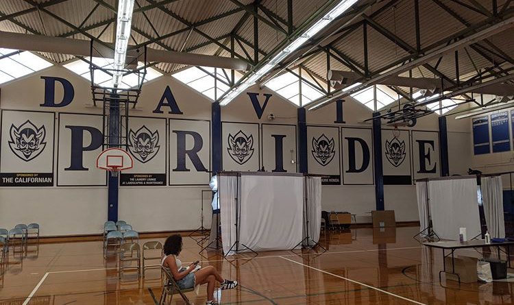 Two booths for taking senior portraits are set up in the South gym, with pairs of chairs lined up on the left for those waiting in line