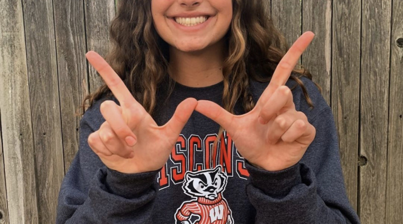 Natalie Bercutt holding up her pointer fingers and thumbs into the letter W