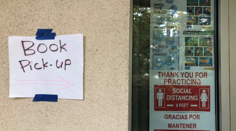 "A paper sign reading ""Book Pick-up"" with an arrow to the right taped on the wall next to a classroom window"