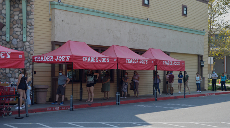 """A line of people waiting around a building under red tents labeled """"Trader Joe's"""""""