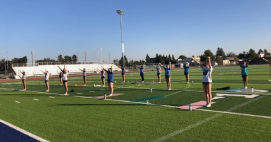 Past competitive cheerleaders practice together on the Davis High field before tryouts