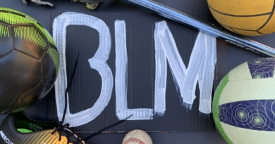 """Sports equipment surround the white paint reading """"BLM"""" on the black background"""