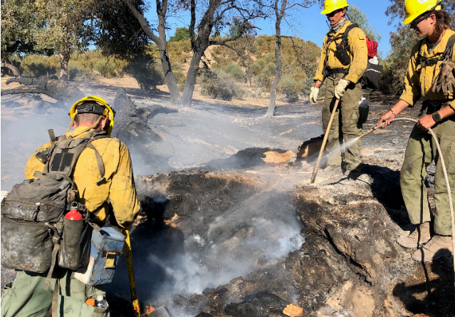 Gieschen working with his crew to spray the flames and slow the spread of the fires