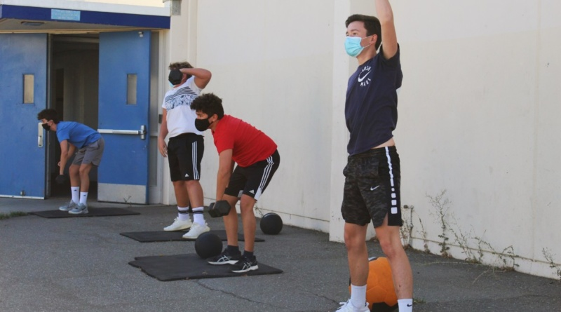 Freshman Alex Gallagher and his water polo team lifting weights in front of the Davis High weight room