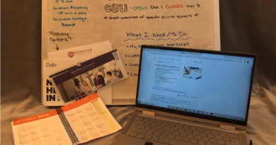 An open laptop and planner splayed out in front of a whiteboard with important dates for the UC and CSU applications