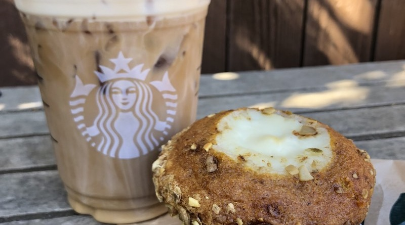 An iced coffee from Starbucks and a pumpkin muffin sit on a Starbucks paper bag on a wooden table.