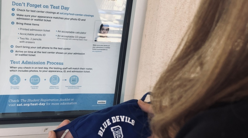 Over the shoulder shot of a student holding up a Blue Devil mask in front of a test day requirements sign