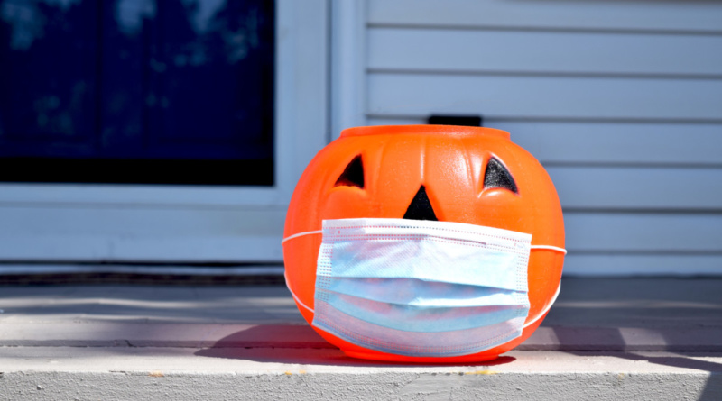 A plastic jack o' lantern sitting on a front porch with a blue face mask