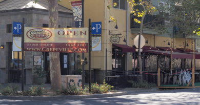 "A huge ""Open"" sign in front of Crepeville in Downtown Davis directs customers to the business's website for online orders and take-out options"
