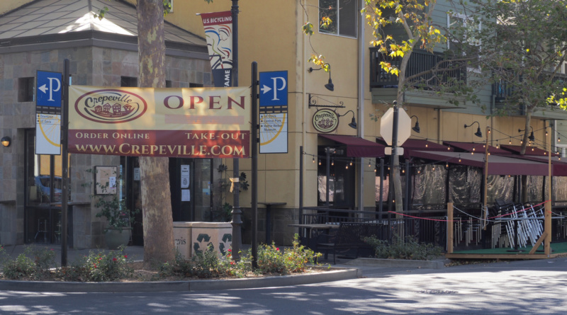 """A huge """"Open"""" sign in front of Crepeville in Downtown Davis directs customers to the business's website for online orders and take-out options"""